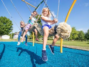 Group of children on group rope swing
