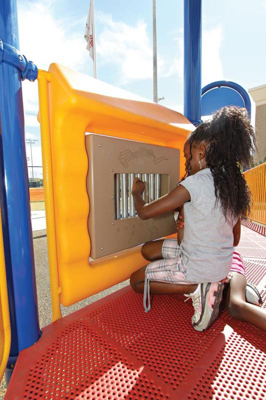 Child playing with outdoor sensory playground equipment